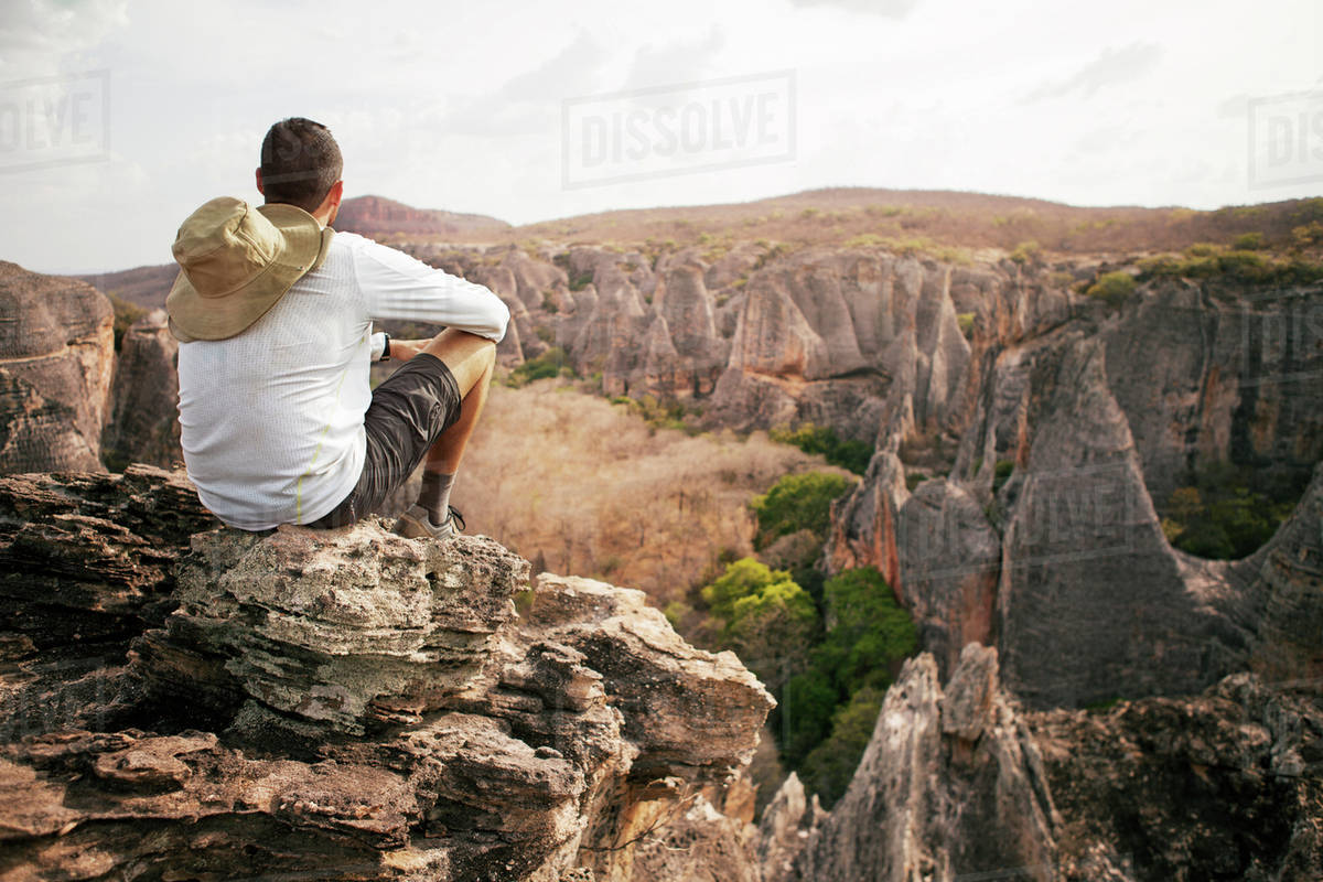 Rear view of man sitting on cliff against mountains in Yosemite National  Park stock photo
