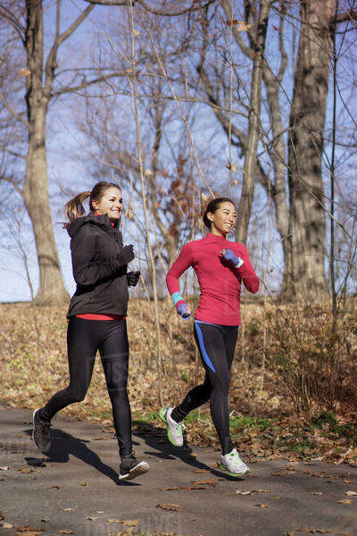 Low angle view of female friends jogging on road against bare trees Royalty-free stock photo