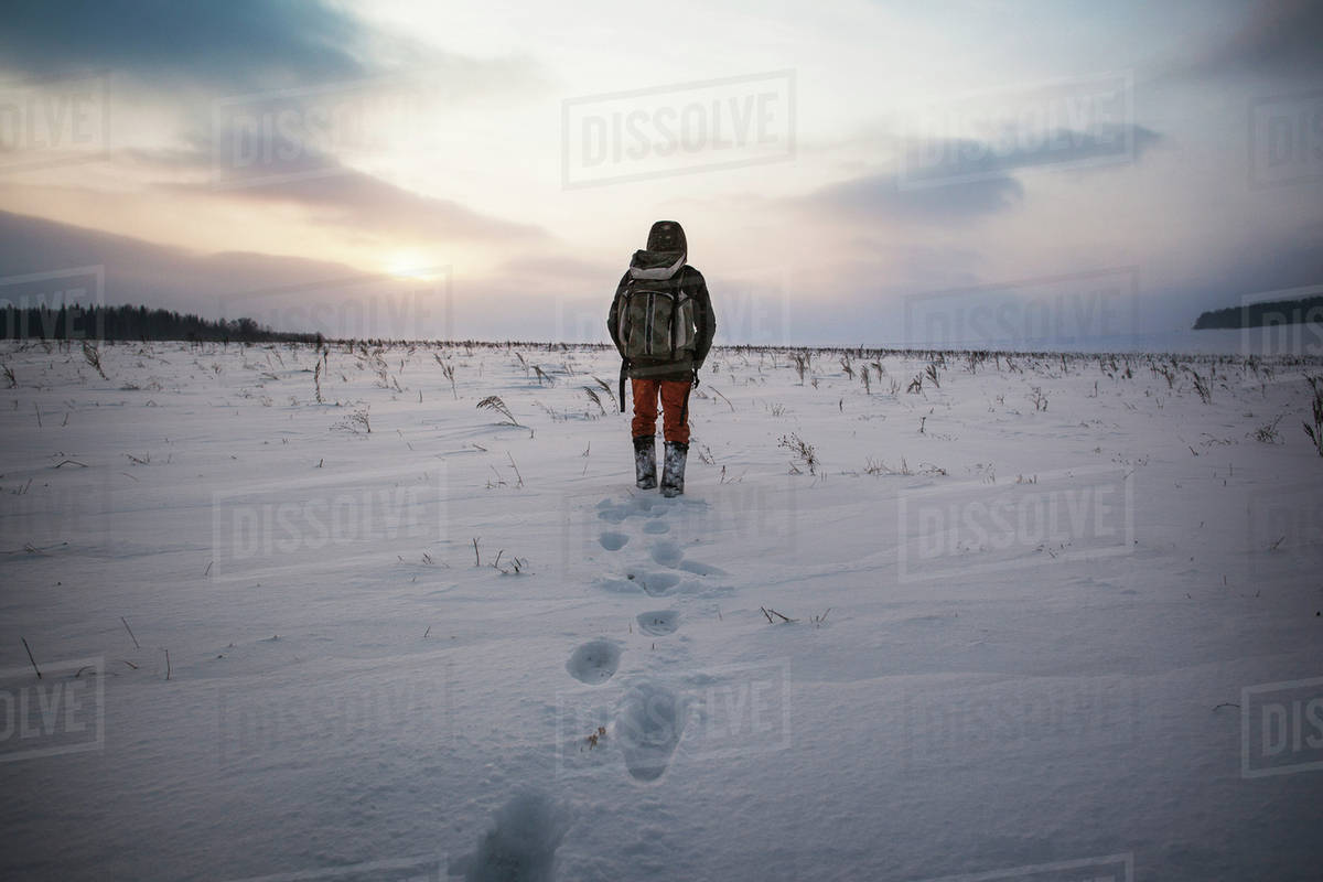 Rear view of man walking on snow covered field against sky Royalty-free stock photo