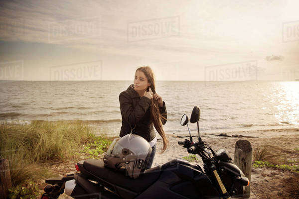Young woman tying hair while standing by motorcycle on beach against sea Royalty-free stock photo