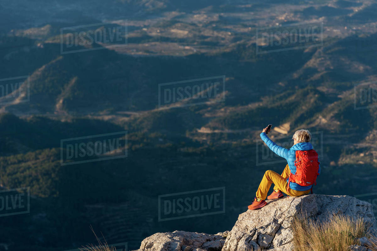 Young woman standing on rocks on top of a mountain making a selfie. Royalty-free stock photo