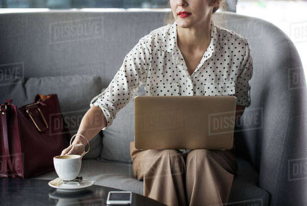 Businesswoman holding coffee cup while working on laptop at restaurant Royalty-free stock photo