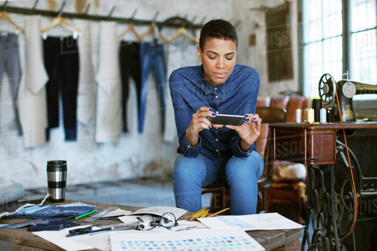 Confident fashion designer using phone while working at workshop Royalty-free stock photo