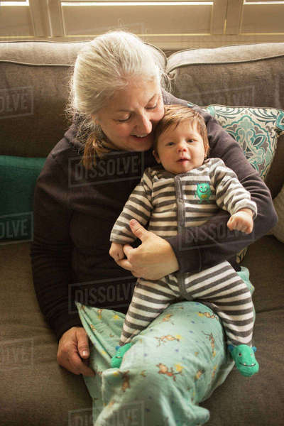 High angle view of grandmother holding baby grandson while sitting on sofa Royalty-free stock photo