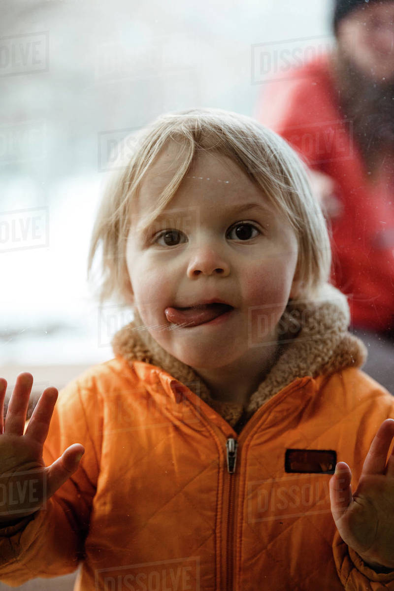 Girl toddler pushes on window looks through glass with twisted tongue Royalty-free stock photo