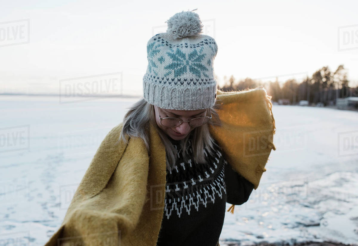 Portrait of woman holding scarf whilst walking on a frozen lake Royalty-free stock photo