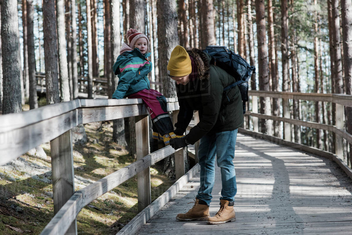 Father helping his daughter put on her shoe whilst walking in the wood Royalty-free stock photo