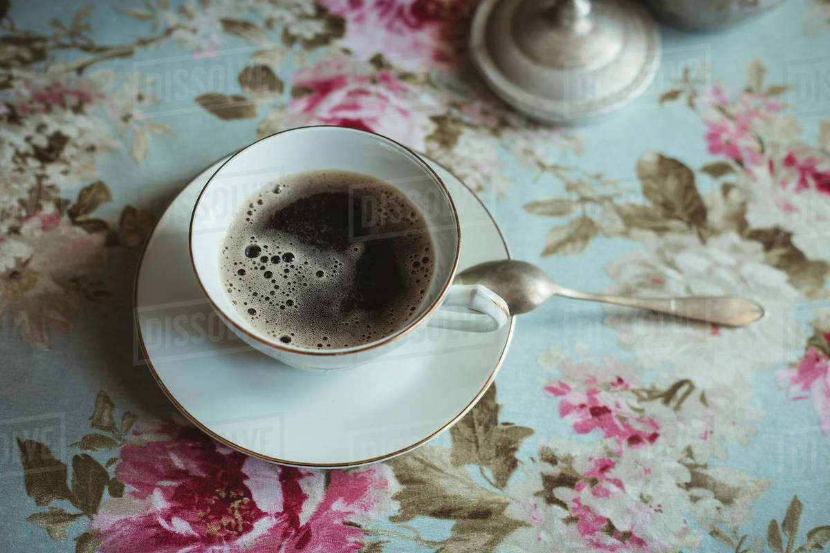 Cup with coffee on table with flower tablecloth Royalty-free stock photo