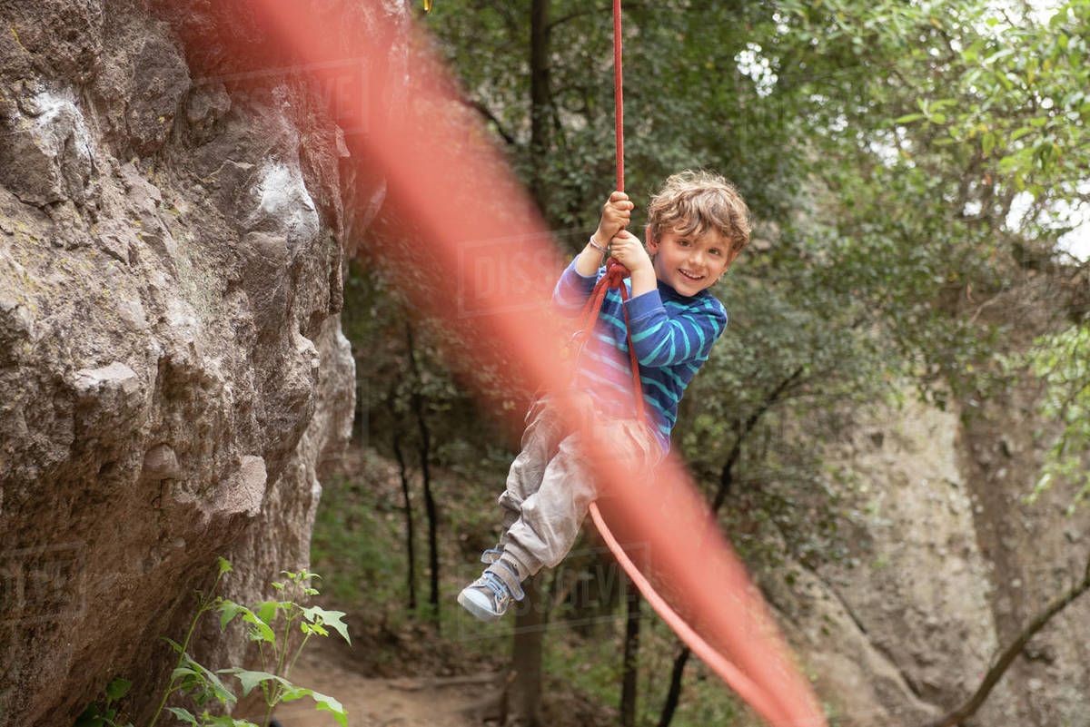 A four year old toddler plays and swings hanging from a climbing rope Royalty-free stock photo