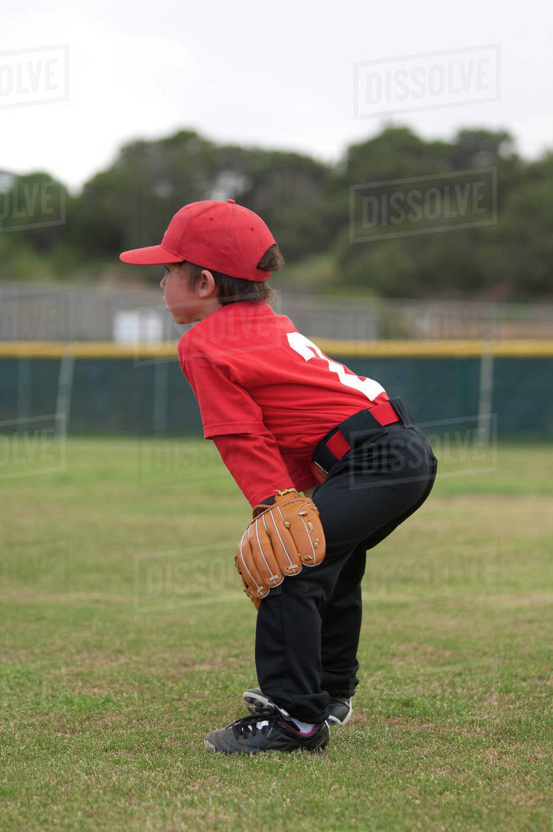 Young boy with his hands and glove on his kees on a baseball field Royalty-free stock photo