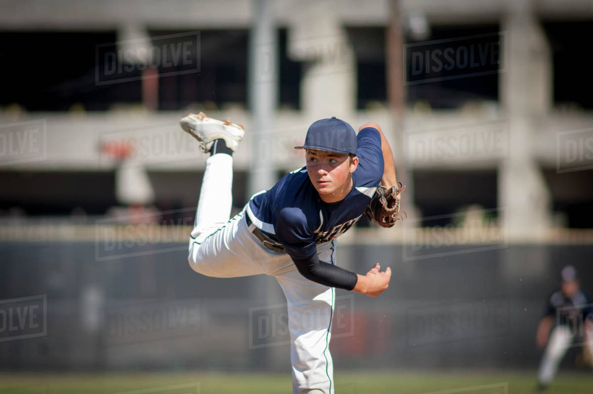 Teen baseball player pitcher in blue uniform on the mound Royalty-free stock photo