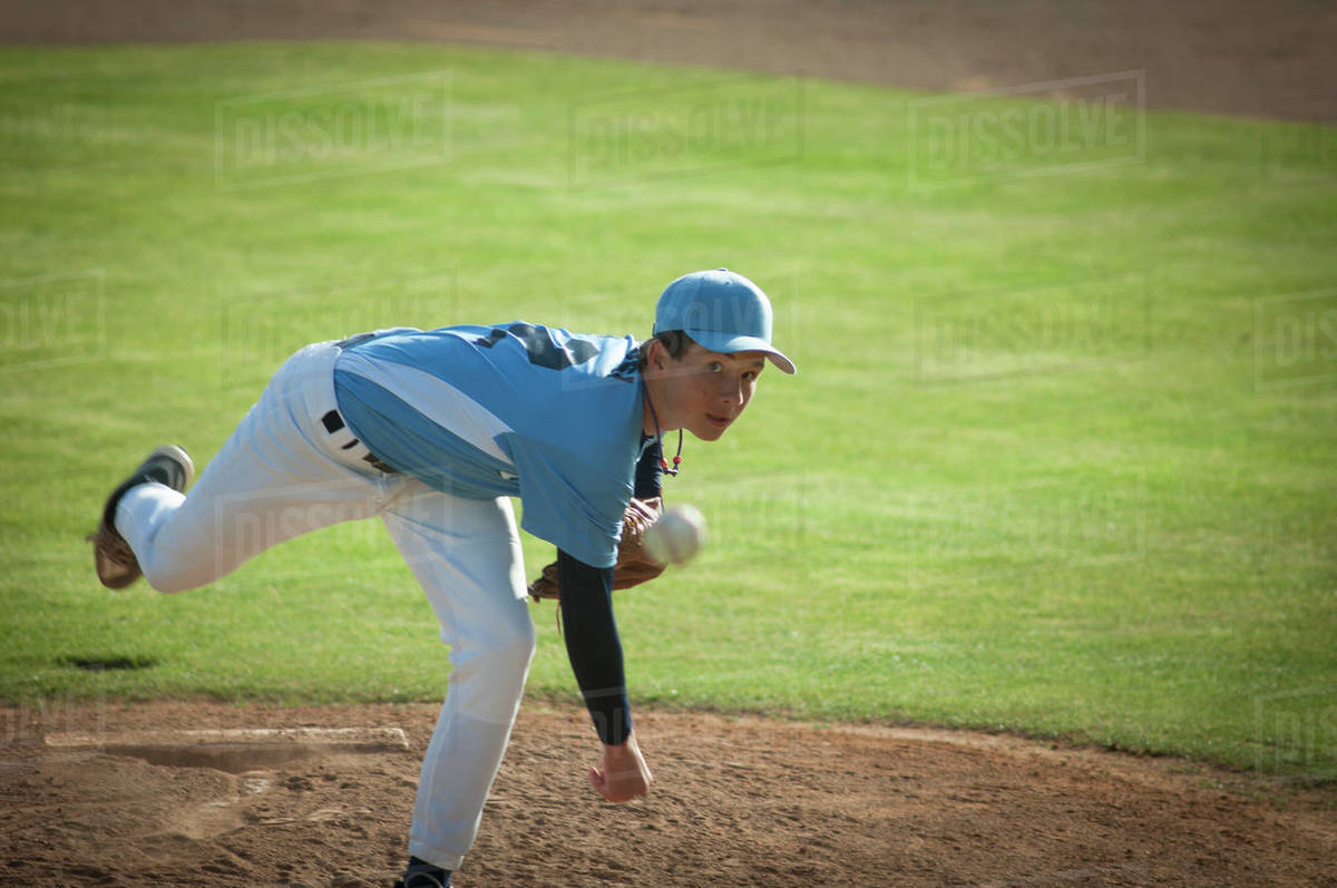 Pitcher in light blue and white jersey during wind up on a baseball field. Royalty-free stock photo