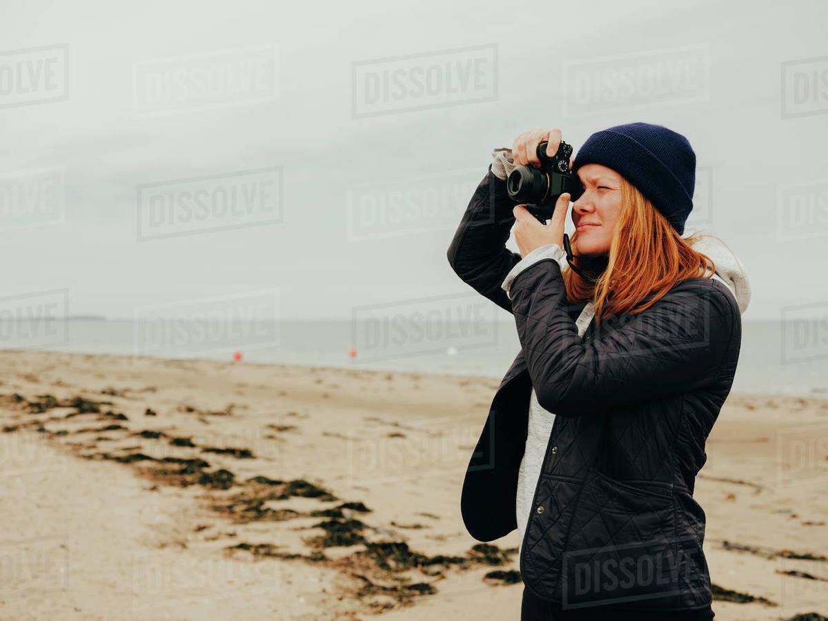 Woman taking photos on beach in Scotland Royalty-free stock photo