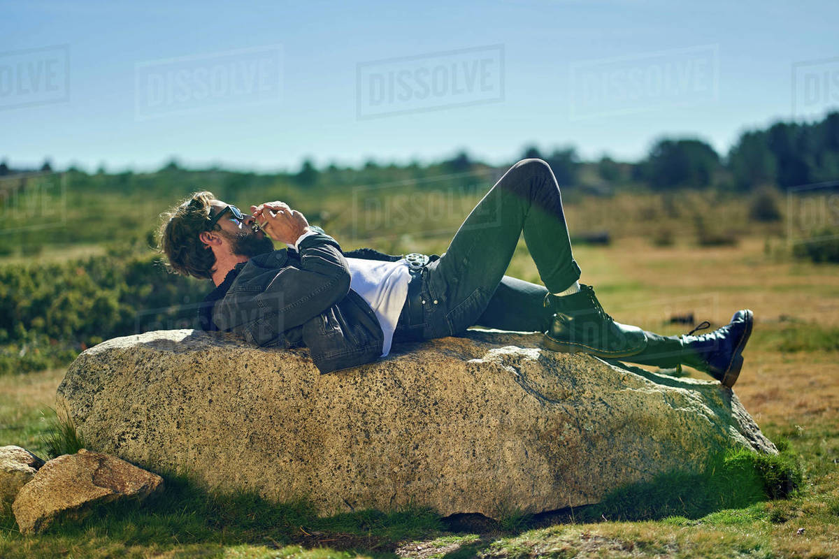 Portrait of young tattoed man lying on a rock smoking Royalty-free stock photo