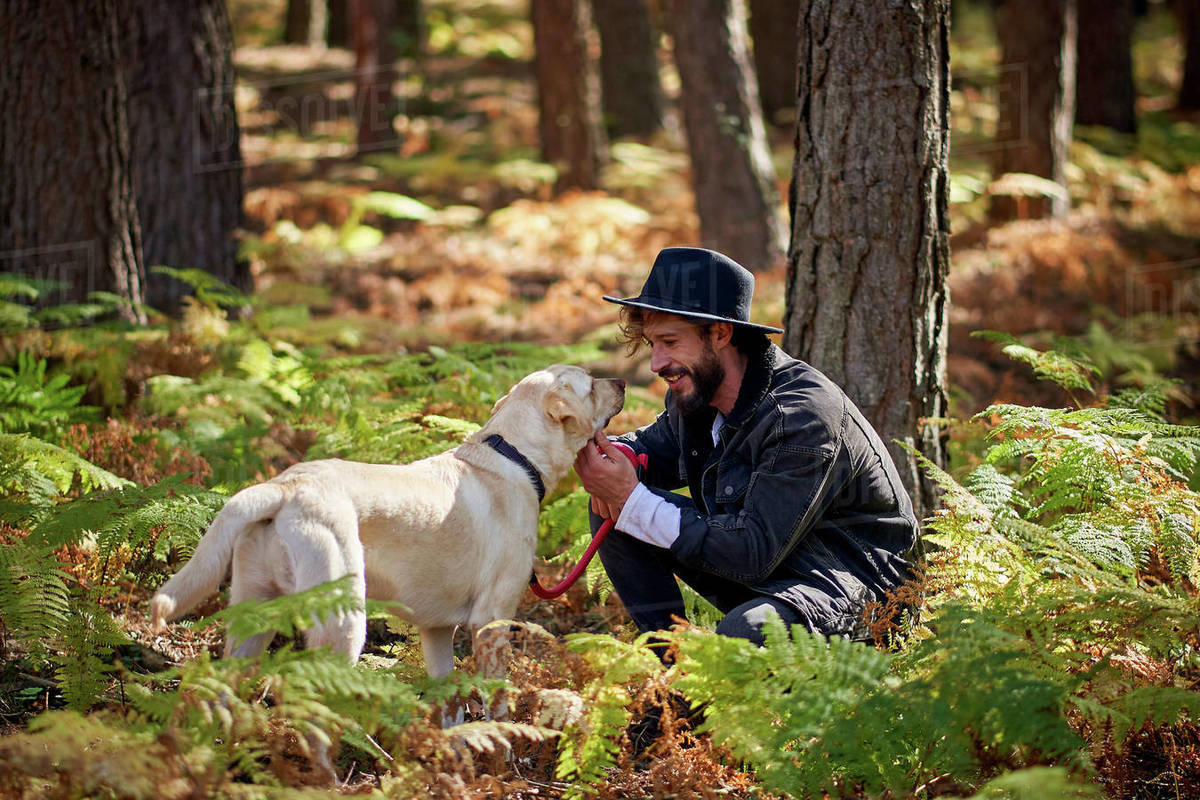 Portrait of young tattoed man with his dog in the forest Royalty-free stock photo