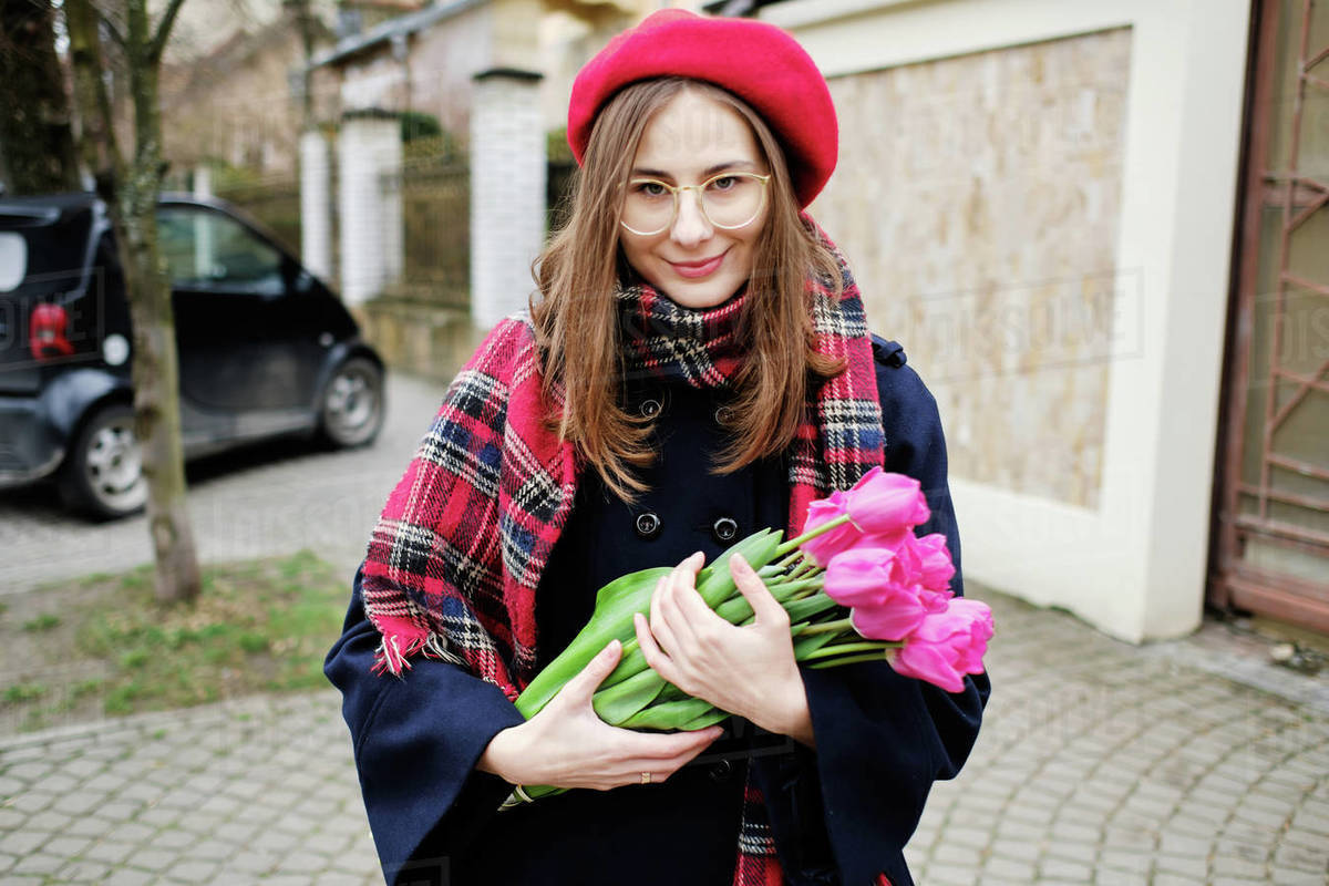 Young french millennial girl in beret and coat with tulips in hands Royalty-free stock photo