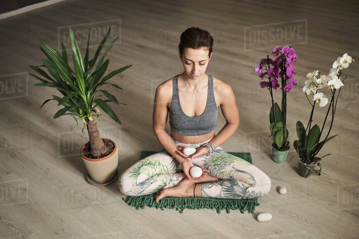Woman doing meditation at yoga studio in the middle of flowers Royalty-free stock photo