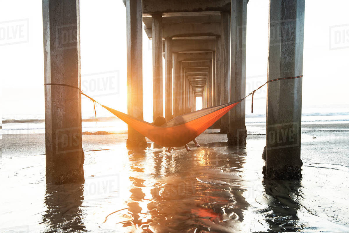 Girls in a Hammock Under a Pier By the Ocean at Sunset in Southe Royalty-free stock photo