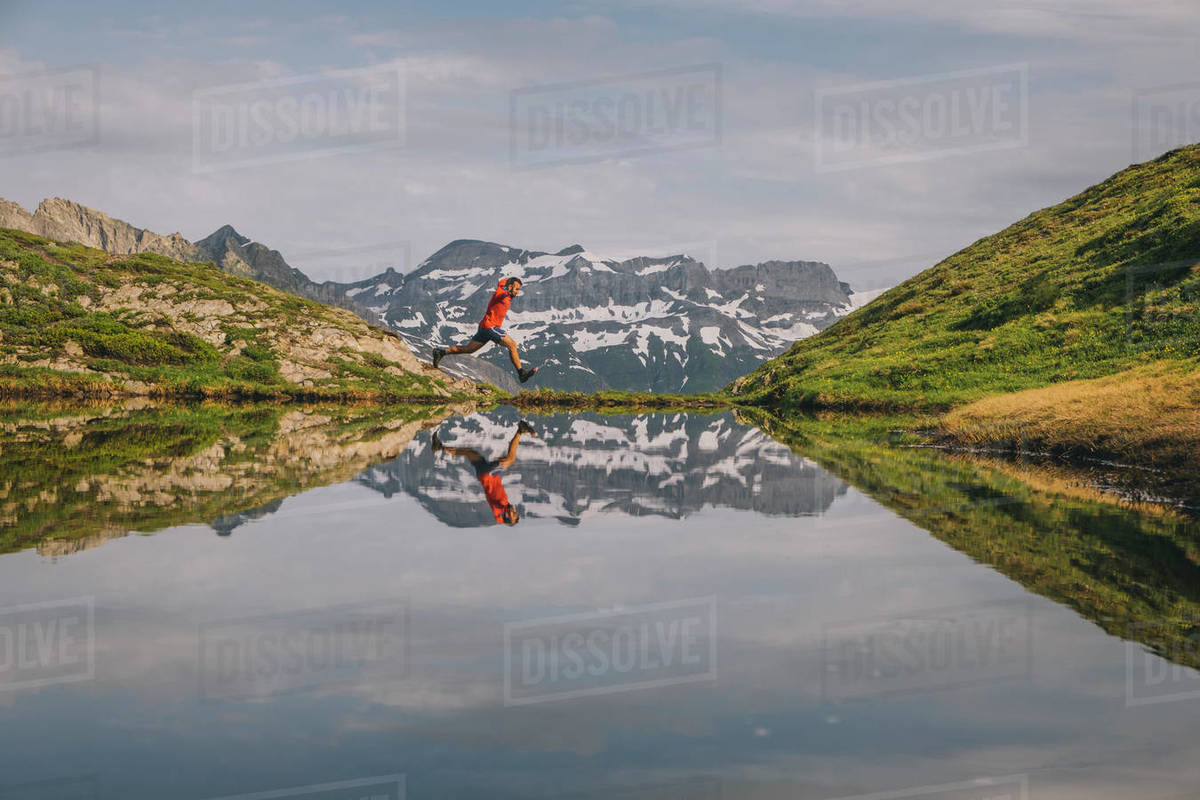 A hiker is jumping reflected in a mountain lake in Chamonix Valley. Royalty-free stock photo