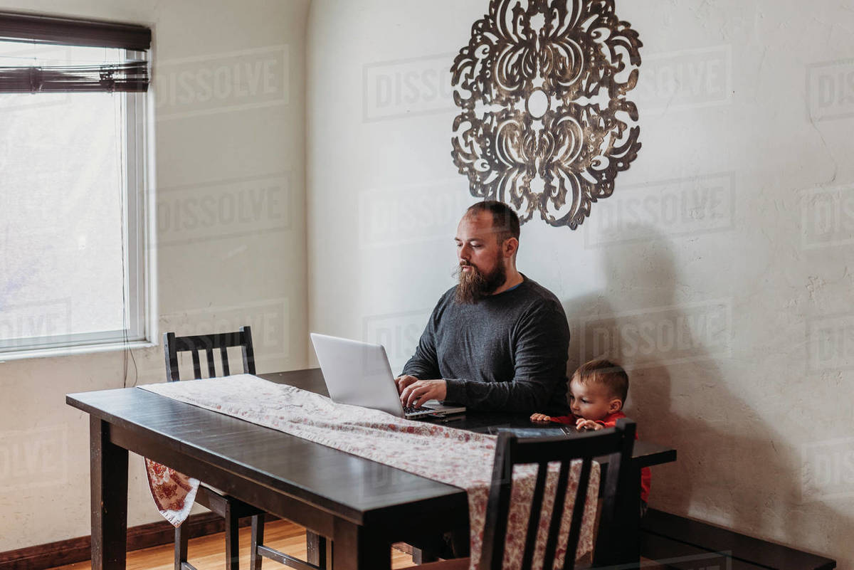 Wide view of father trying to work from home with toddler standing Royalty-free stock photo