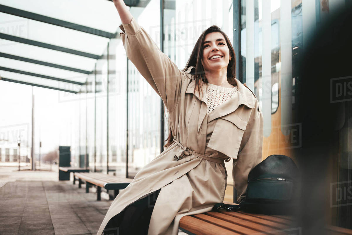 Positive young woman sitting at a public transport stop and waving Royalty-free stock photo
