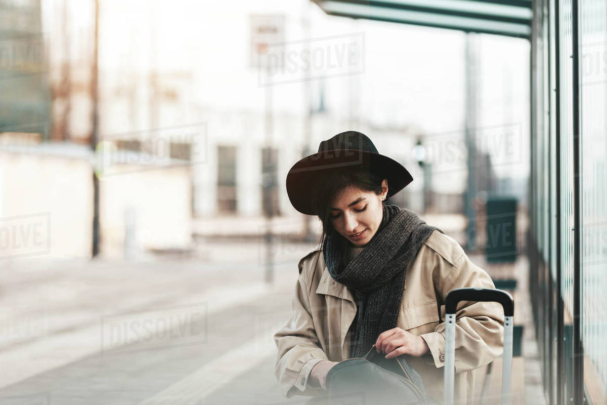Casual young woman sits at a public transport stop Royalty-free stock photo