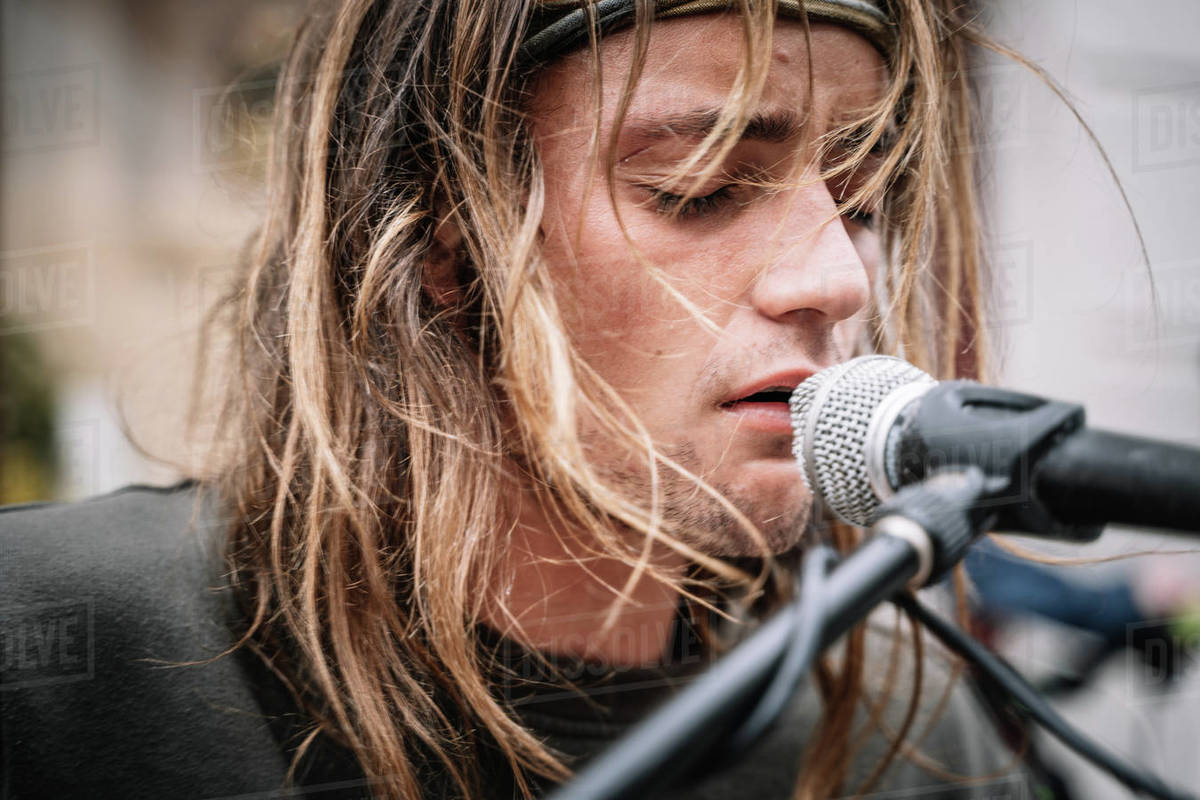 Detail of the face of a young rocker singing with emotion in the street Royalty-free stock photo