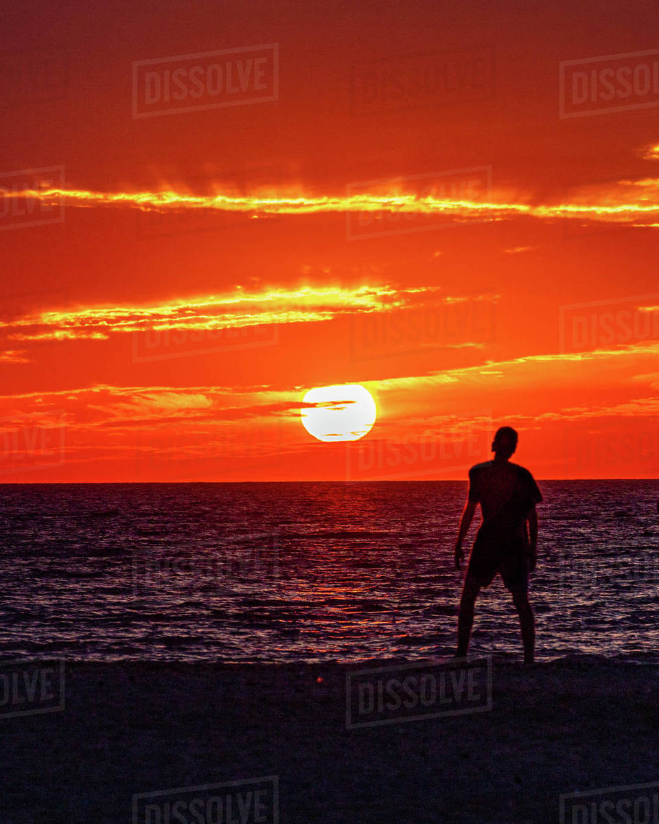Boy watching sun set along the ocean shoreline admiring the fire sky. Royalty-free stock photo