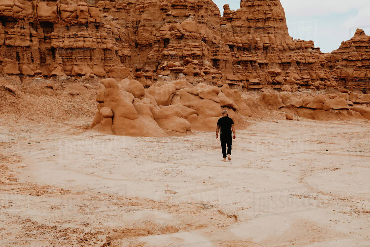 Man walking alone among hoodoo rocks in Goblin Valley Royalty-free stock photo