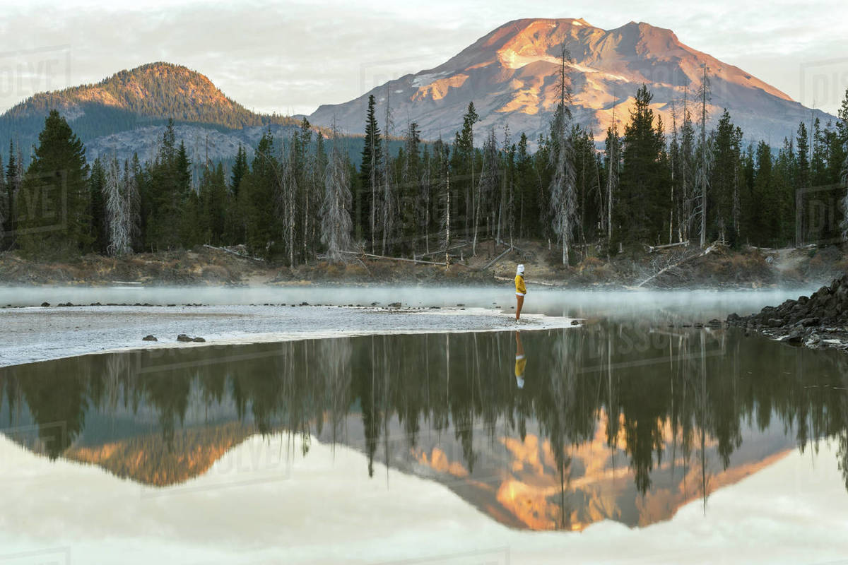 Young woman looking at a mountain reflecting in a lake Royalty-free stock photo