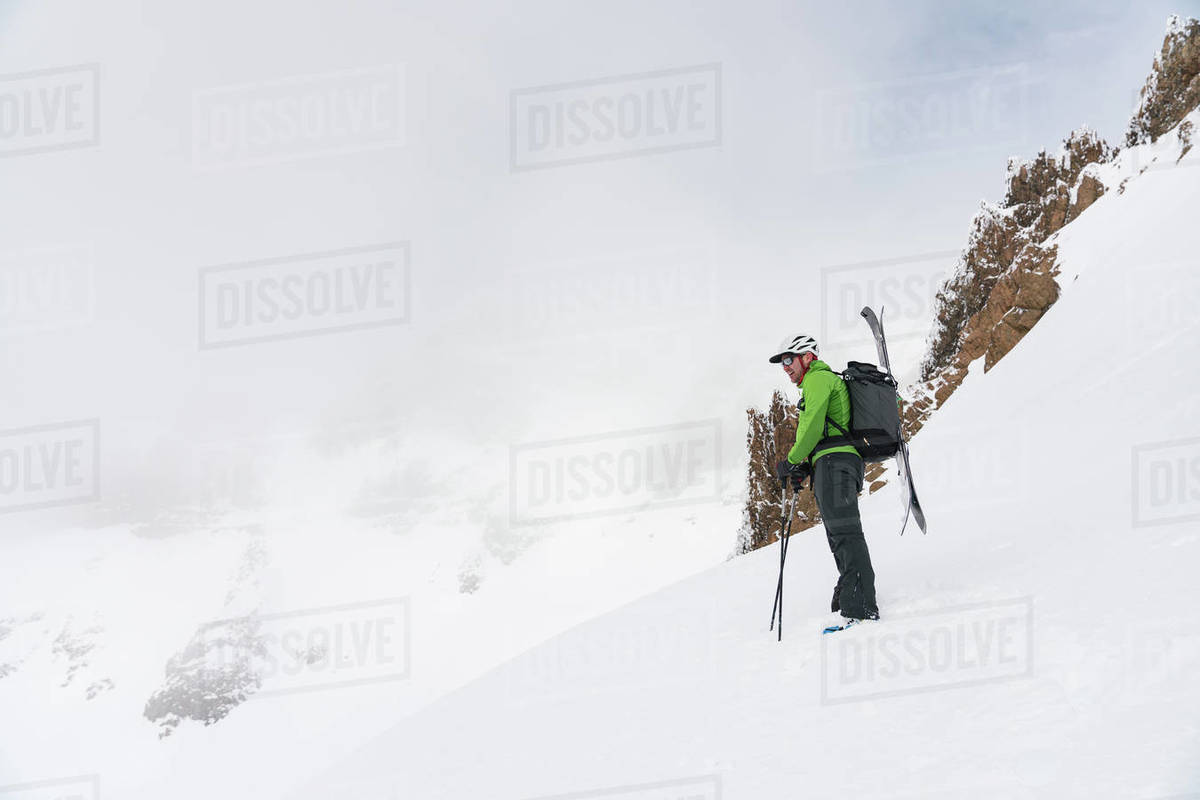 Skier standing at top of line looking out over foggy mountains Royalty-free stock photo
