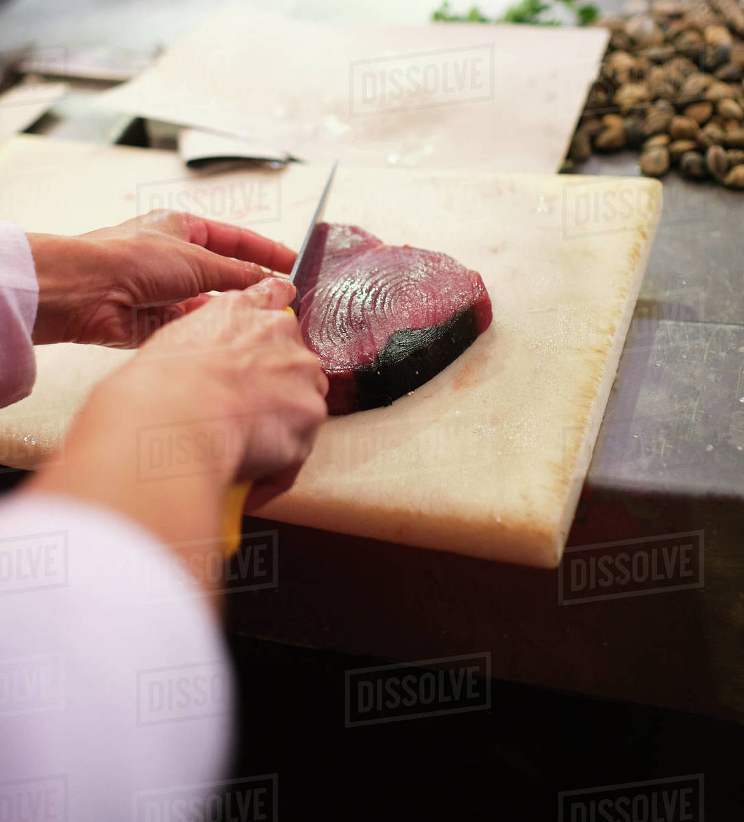 Young woman cuts up a red fish in her fishmonger's Royalty-free stock photo