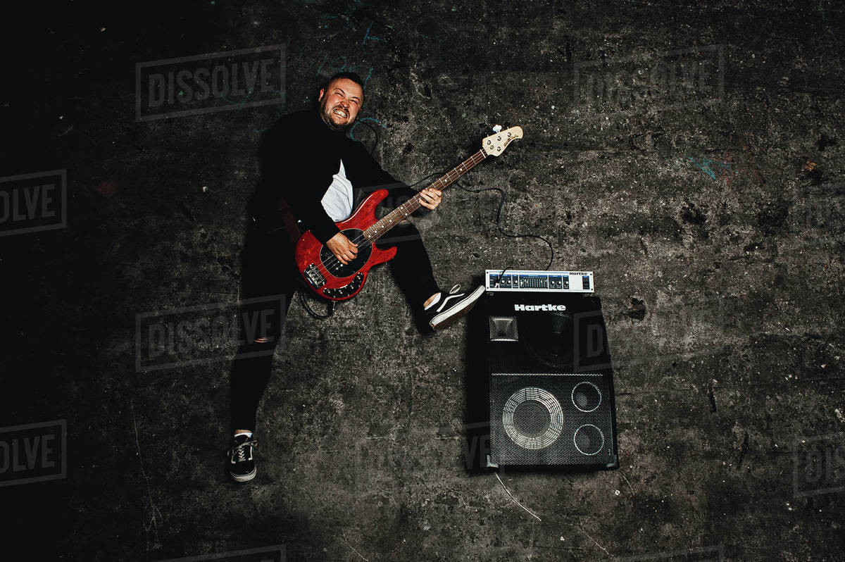 Bass Player with Red Guitar on the ground Royalty-free stock photo