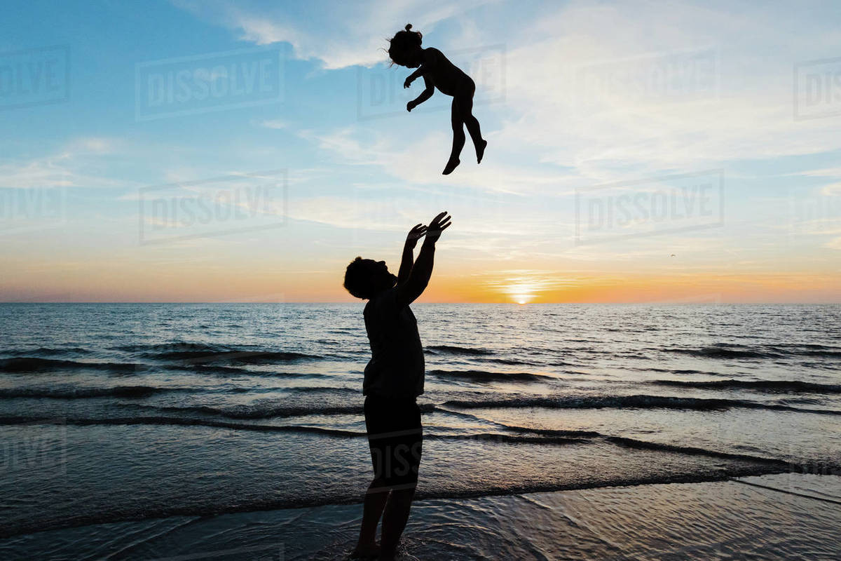 Father throws his daughter into the air at sunset on beach vacation Royalty-free stock photo