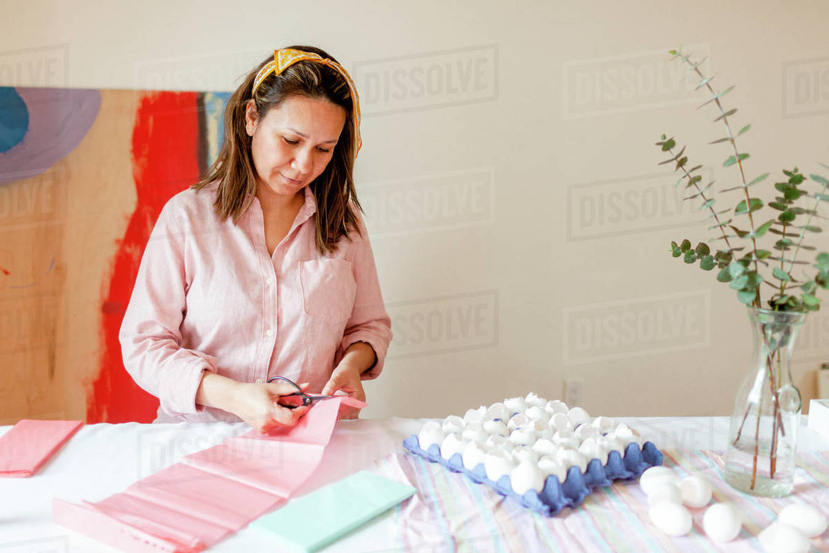 Peaceful woman cutting craft pink paper by eggshells at home Royalty-free stock photo