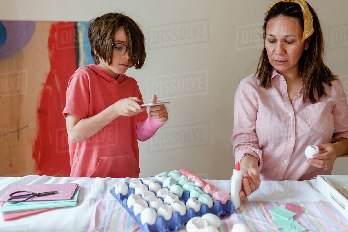 Boy taking photo while mom craft confetti egg project Royalty-free stock photo