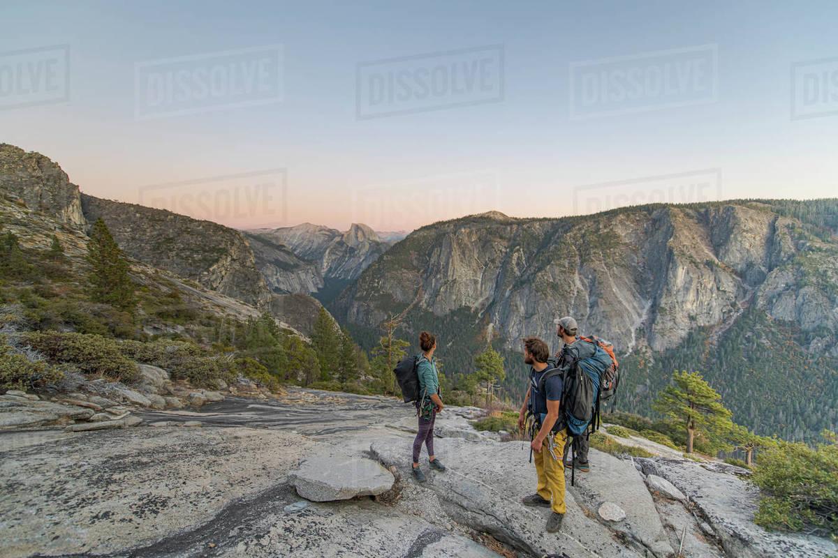 Three hikers looking at Half Dome from El Capitan sunset Yosemite Royalty-free stock photo