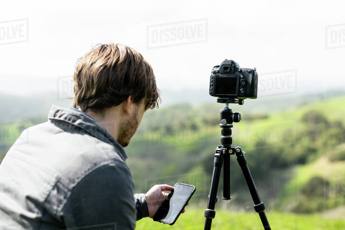 Person using smartphone app to control camera on tripod outdoors Royalty-free stock photo