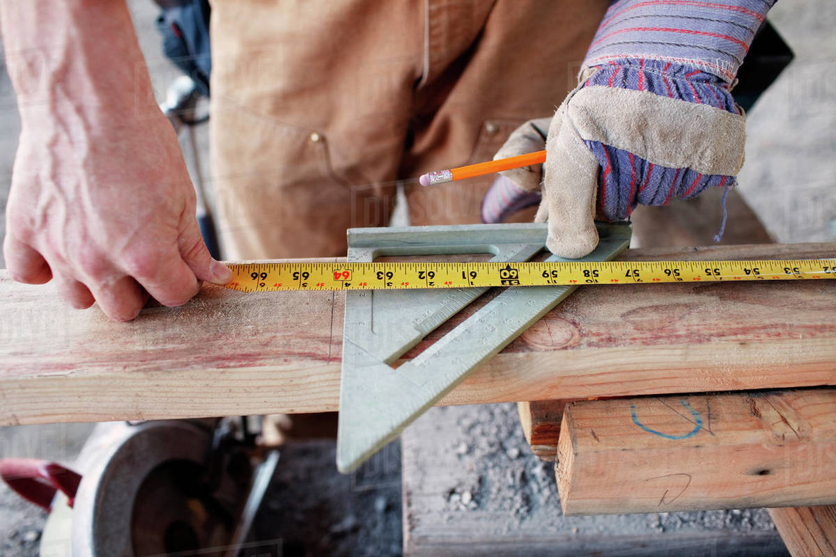 Closeup of male construction worker measuring wood for cut Royalty-free stock photo