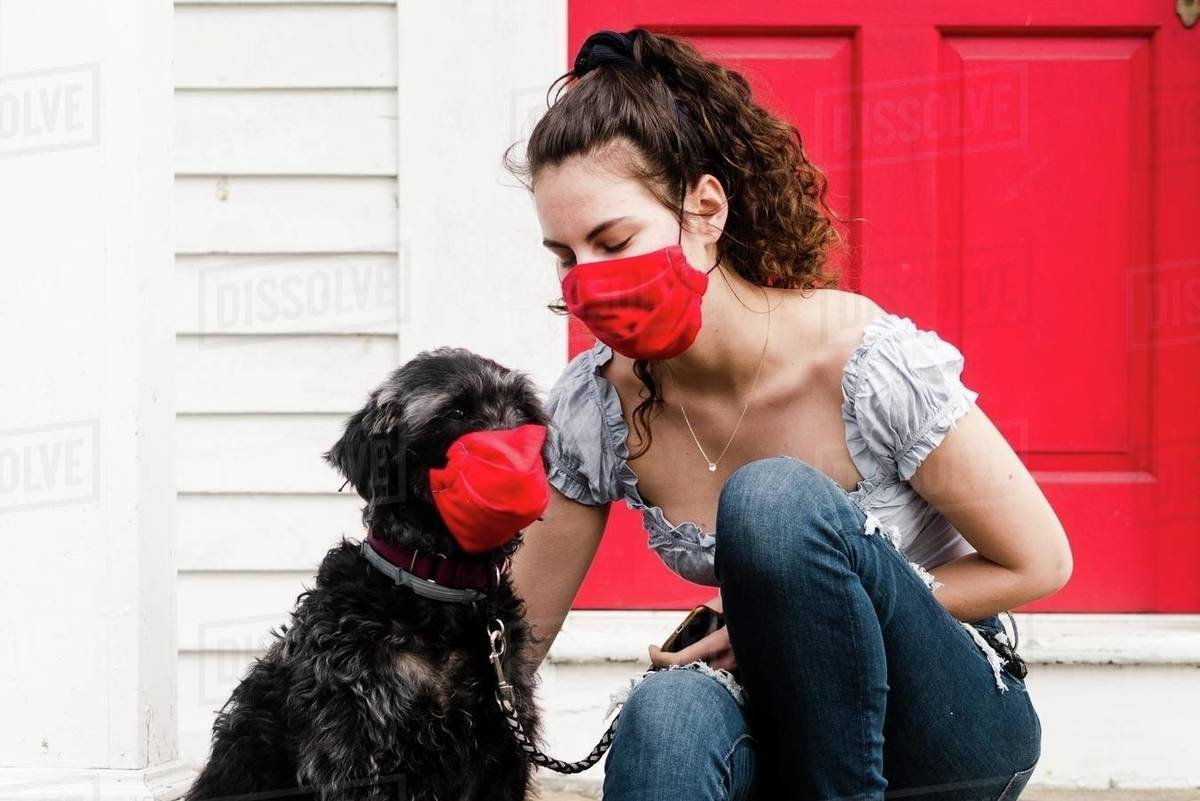 Young woman and dog wearing read mask during COVID-19 pandemic Royalty-free stock photo