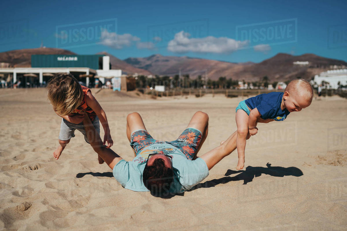 Father and children working out and playing at the beach on sunny day Royalty-free stock photo