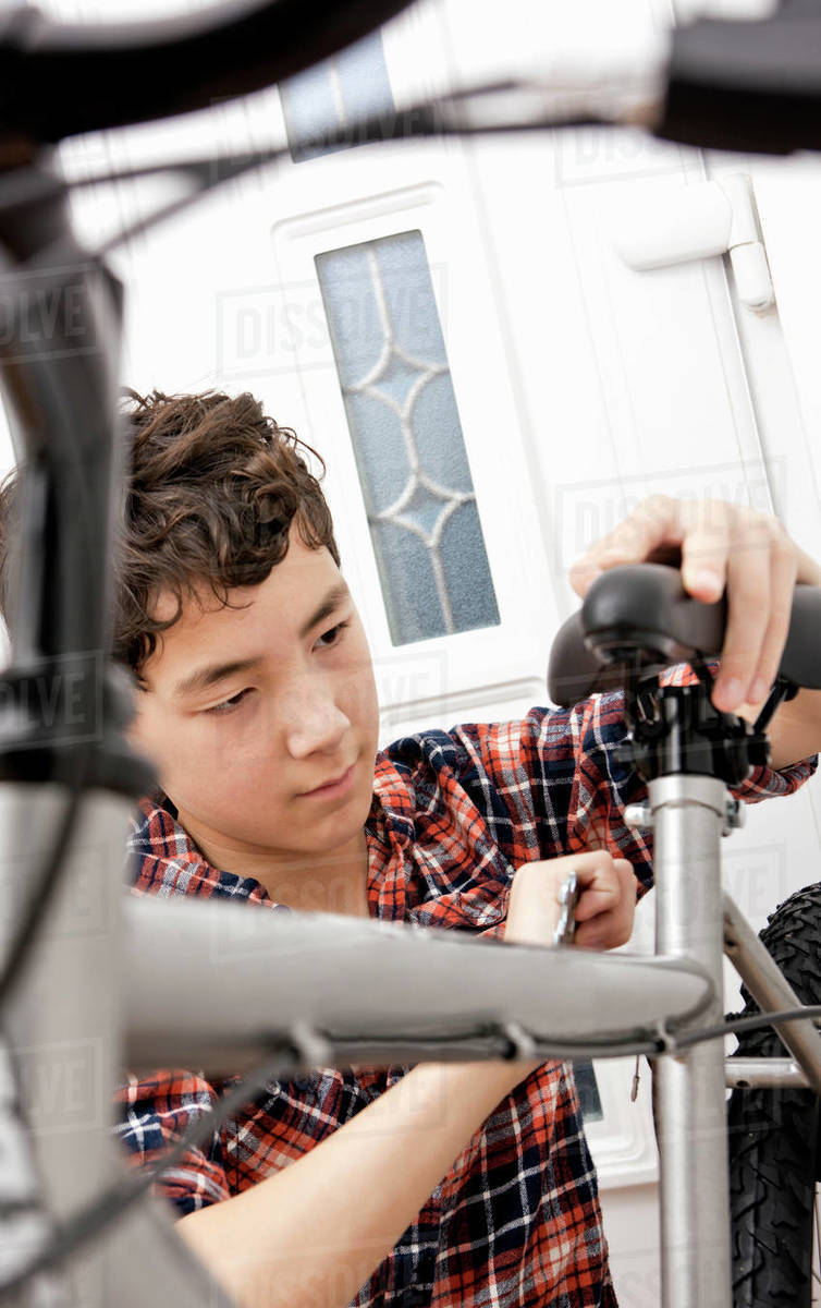 Boy is assembling his new mountain bike at home Royalty-free stock photo