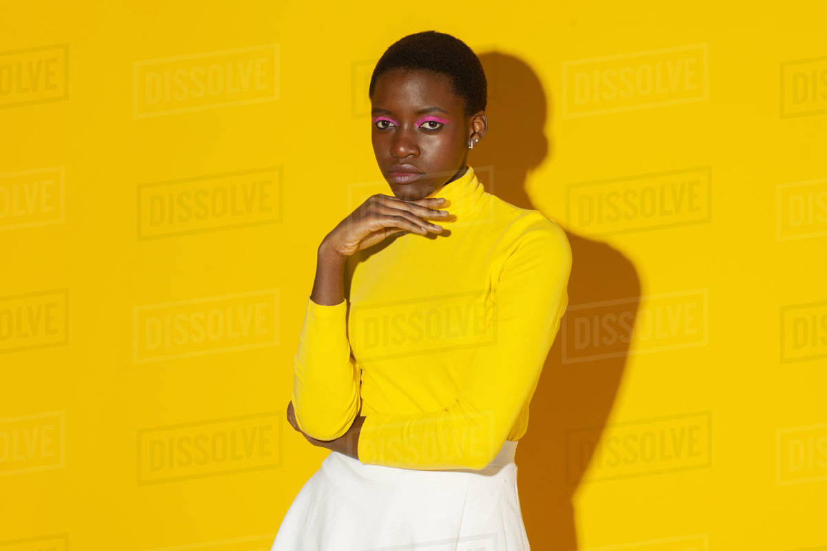 Young fashionable woman, total yellow style on yellow background Royalty-free stock photo