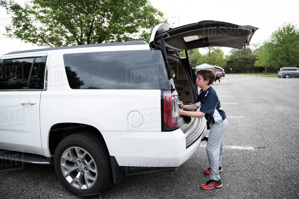 Teen Boy Loads Baseball Equipment Into Rear of White SUV After Game Royalty-free stock photo