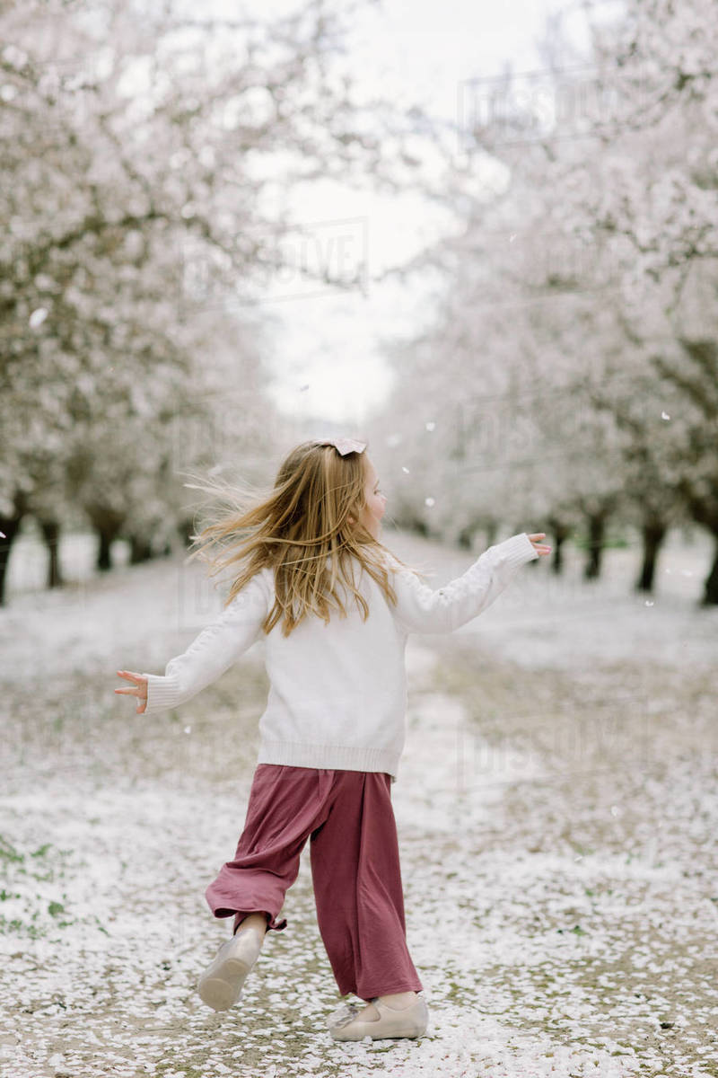 Preschool girl dancing in an almond orchard Royalty-free stock photo