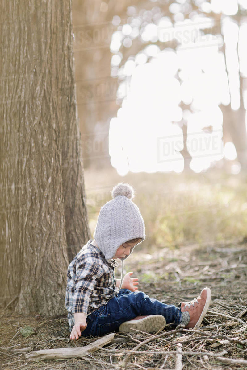 Toddler boy sitting against a tree in the woods Royalty-free stock photo