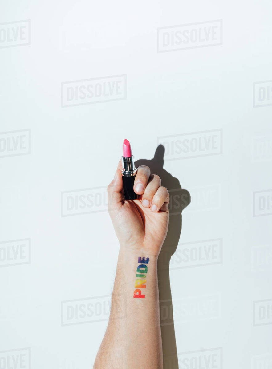 Gay guy's hand with a tattoo that says pride and nail polish. Royalty-free stock photo