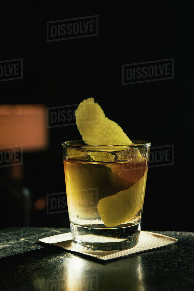 Old fashioned cocktail with citrus in sun beam at bar top Royalty-free stock photo