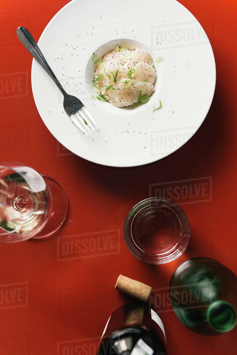 Thin sliced scallop ceviche on red table top in French restaurant Royalty-free stock photo