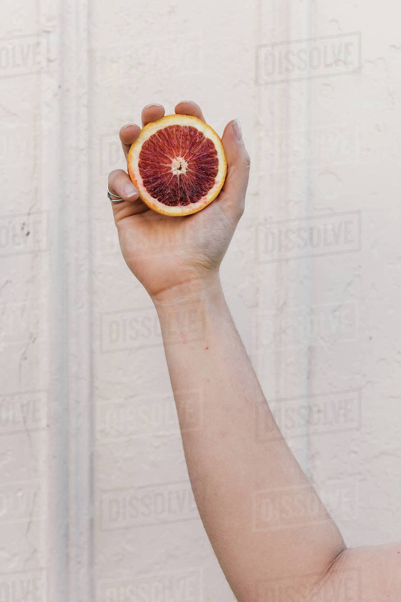 Woman holding in hand a cut open blood orange Royalty-free stock photo